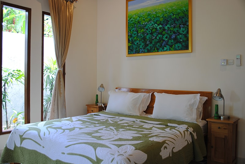 The master bedroom with king bed has a garden view.