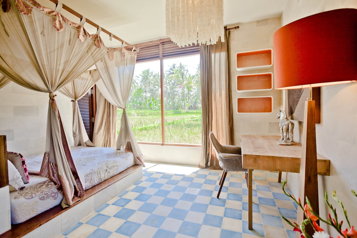 The ground floor master bedroom with windows to rice paddies and jungle
