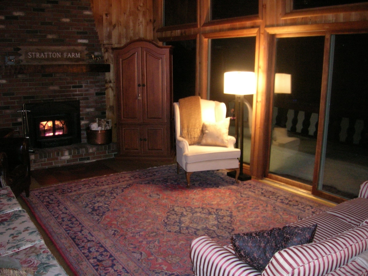 The living room offers seating for 8-10 with the wood-burning fireplace