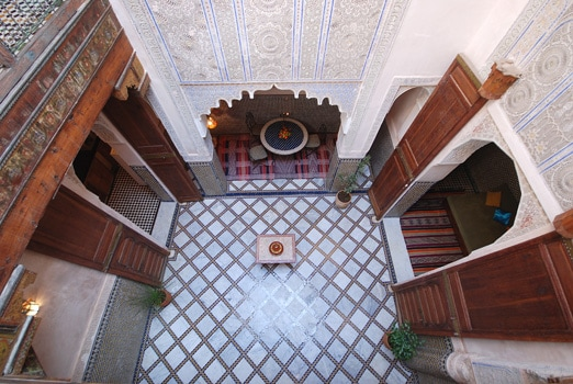A nice look from the upstaires balcony, it shows the courtyard, painted wood, old ceder wooden doors, Zellij mozaic, and sculpted plaster.