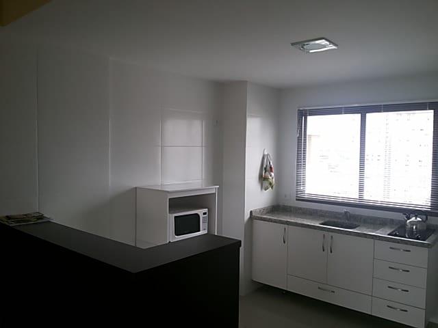 Cozinha - Área central da cozinha com detalhe da pia e fogão elétrico e lado esquerdo com detalhe do micro ondas.
