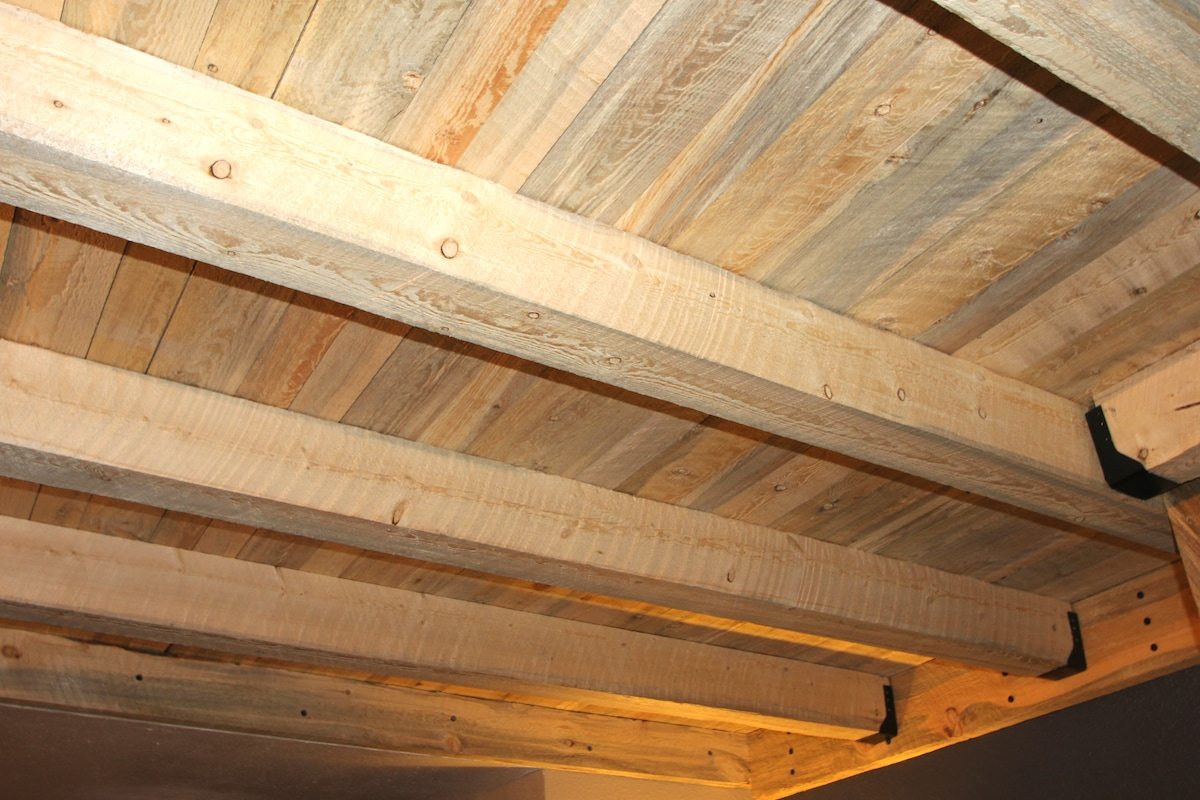 Reclaimed beetle-kill wood beams/ceiling warms up the room