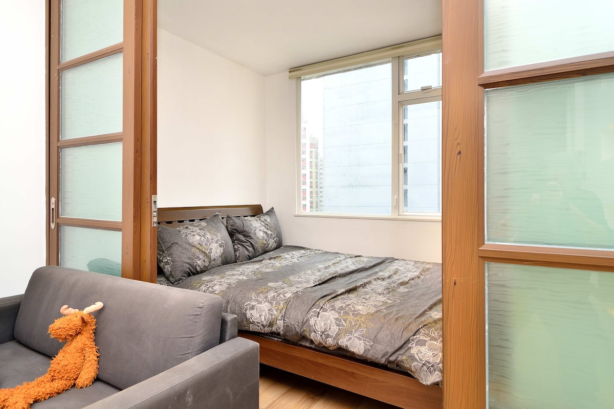 Comfortable double bed with large window overlooking Central, Hong Kong