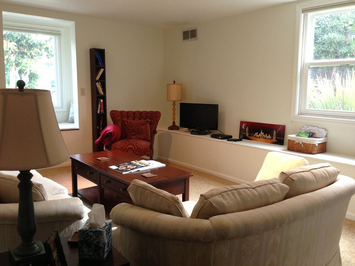Large and bright living room with window seat, TV and loads of restaurant ideas, maps, and  Bay Area events to peruse