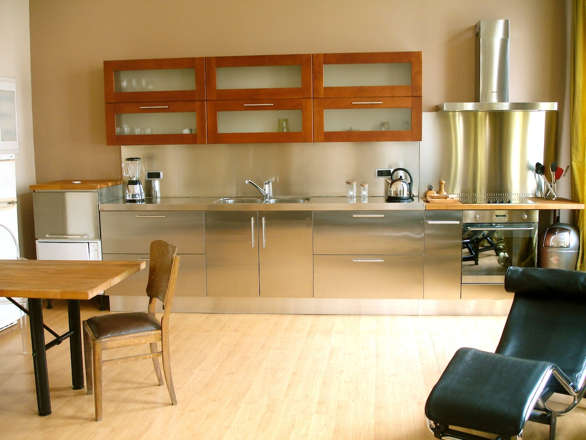 Full view of kitchen area. Italian design kitchen in cherrywood and inox.