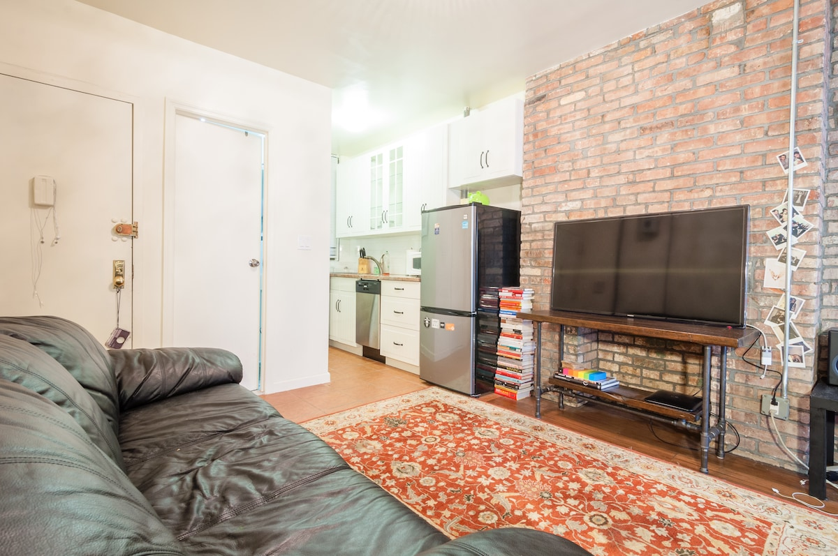 Large clean living room with brick exposure