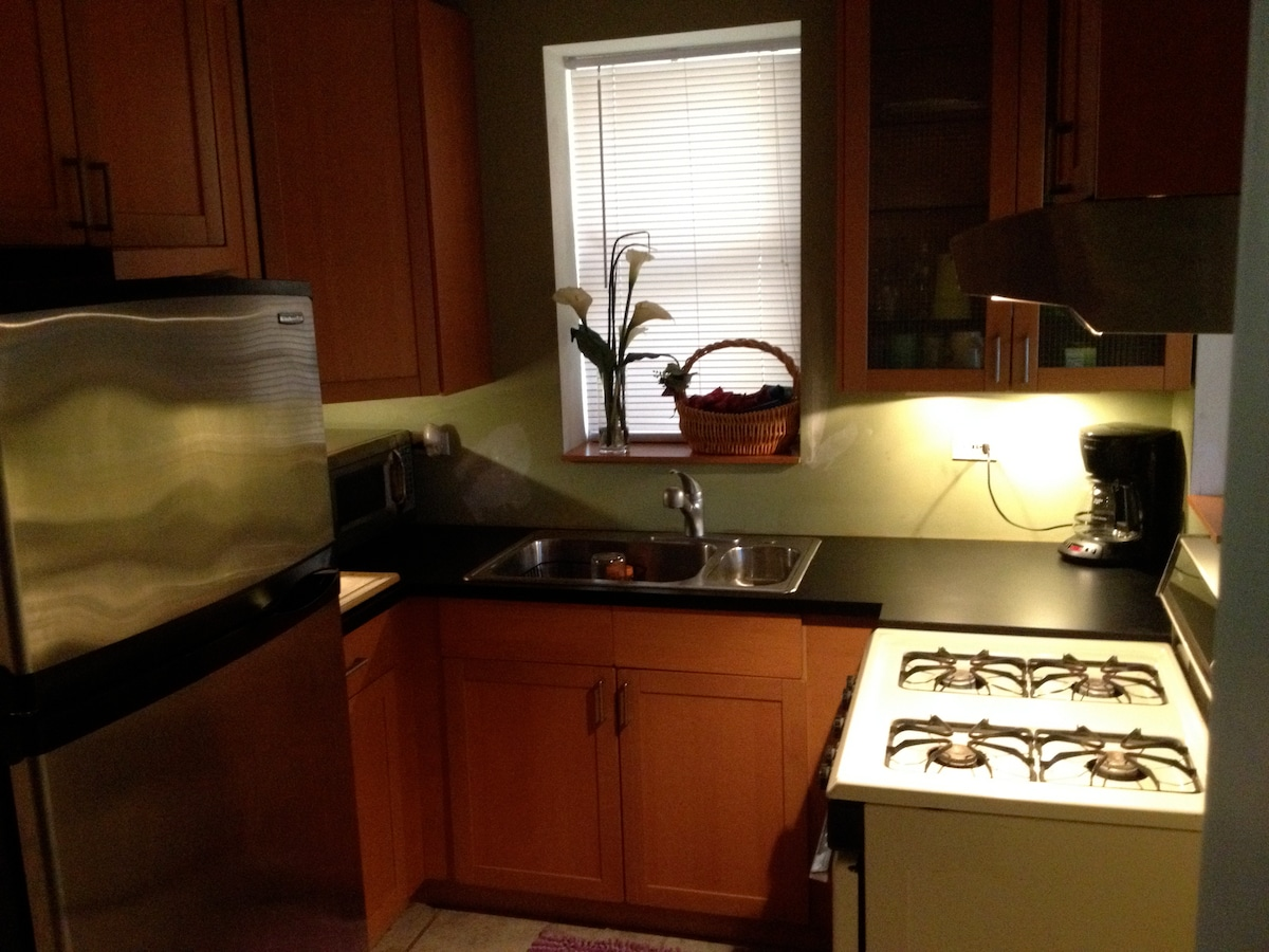 Kitchen with refrigerator, microwave, stove, coffee maker, and more.
