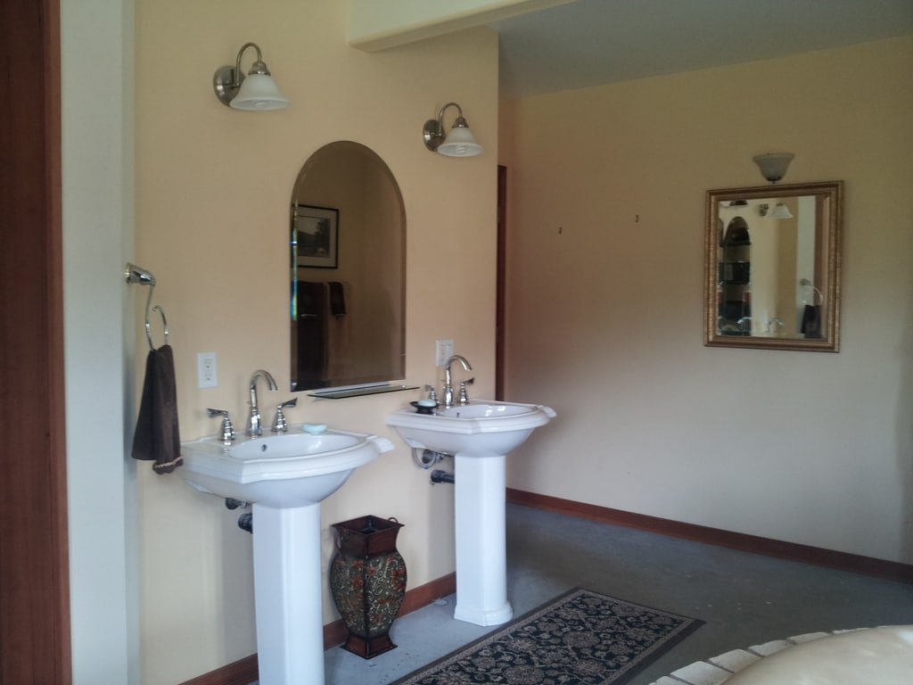 Twin pedestal sinks in expansive bathroom, with shower and separate toilet room