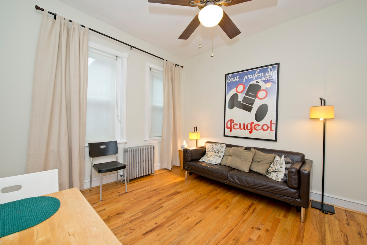 The living room has a sofabed, dining table with chairs for 4, a ceiling fan, Bose radio, and large windows.