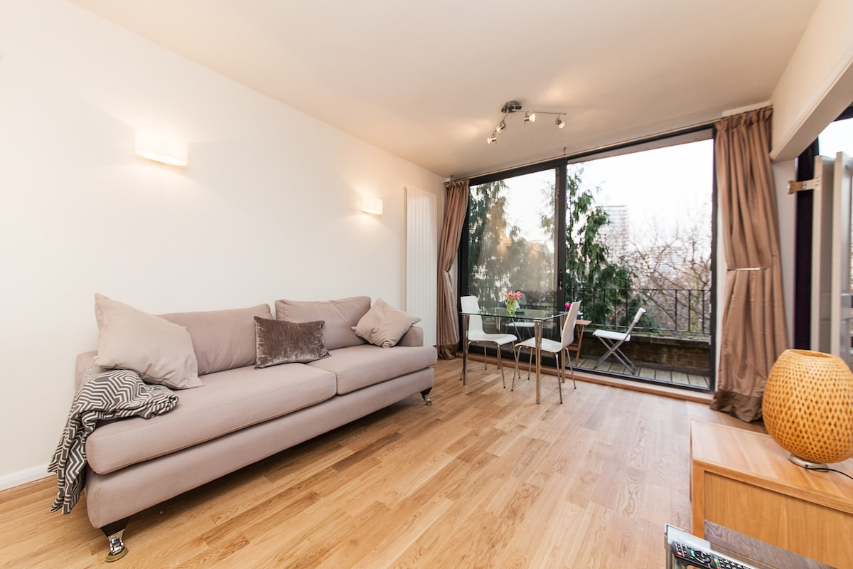 Large living area / lounge. Solid oak flooring and floor to ceiling sliding windows that lead to decked balcony