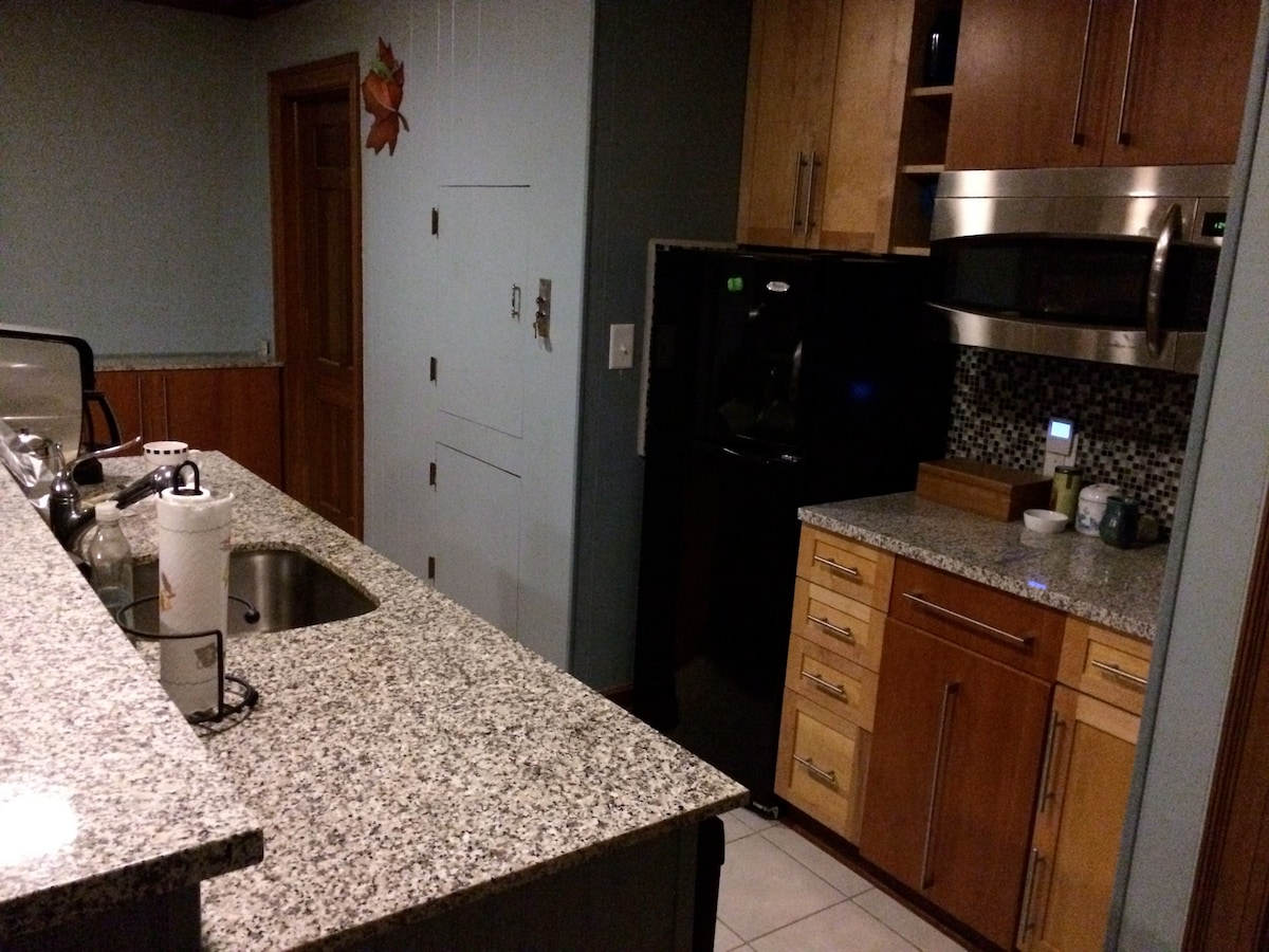 Kitchen bar, sink, coffee maker, convection oven, refrigerator & freezer.