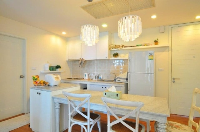Well-lit, fully equipped kitchen.