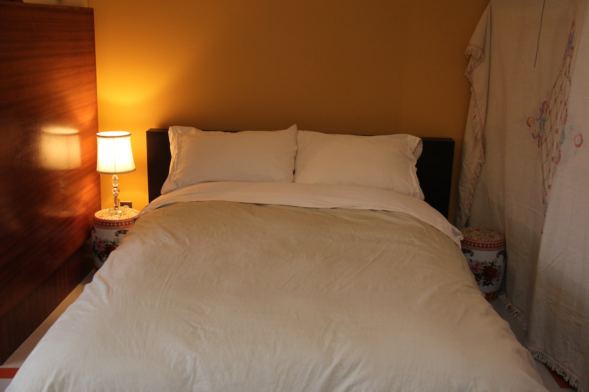 The double bed with the incredible organic mattress flanked by mahogany built-ins and antique bedspread.