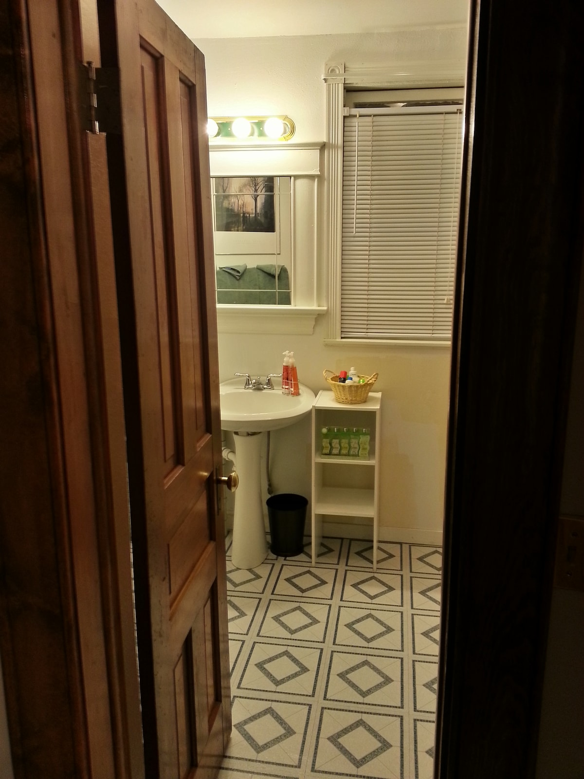 The bathroom as a single-sink vanity, jetted tub/shower and separate water closet with pull-chain toilet.