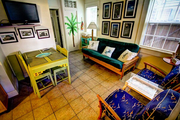 Comfortable Seating area with a futon, table for 4, and two vintage chic chairs
