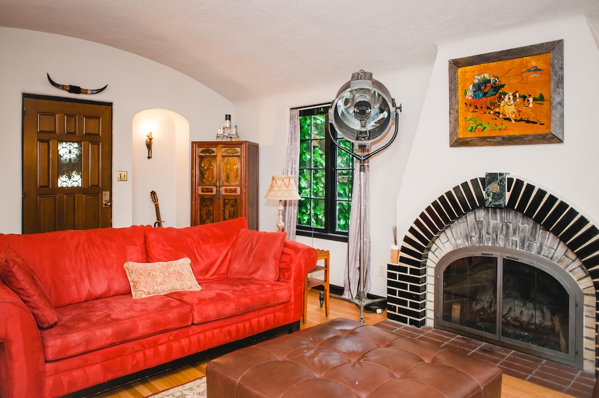 Front room flows into a large mission style den/family room complete with original working fireplace and additional separate front entrance.