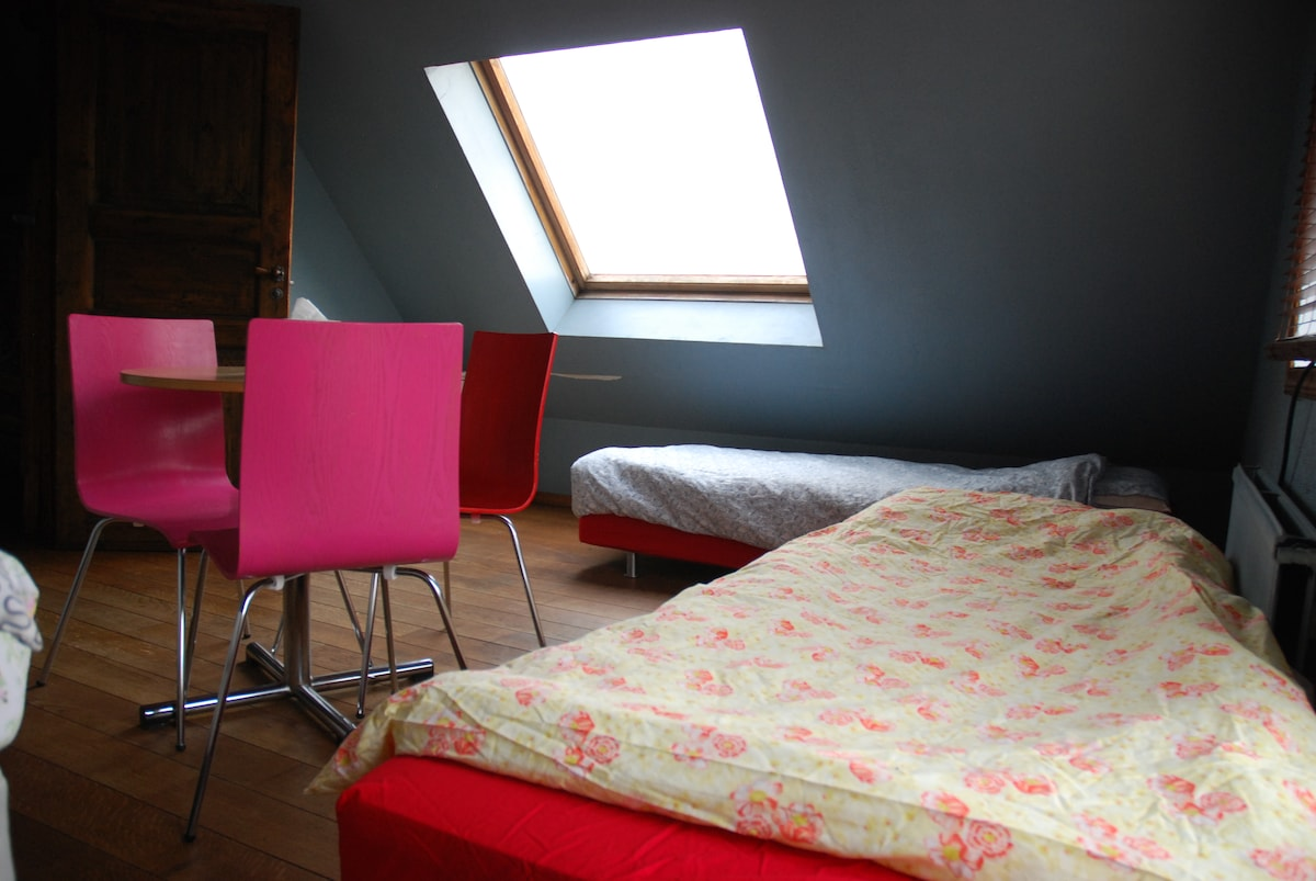 The room has one double bed and two single beds.