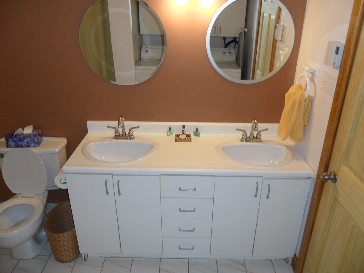 Large bathroom with double sinks, shower/bath as well as in-unit washer + dryer.