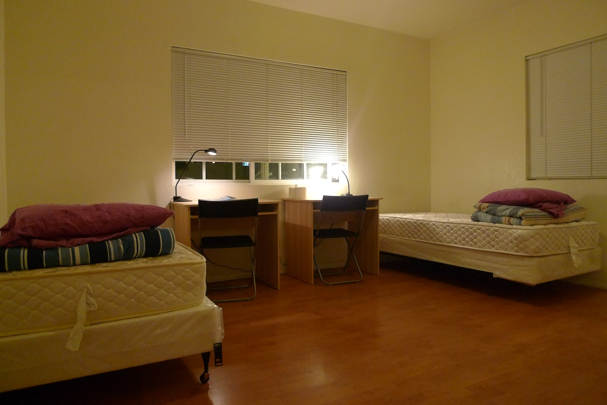 A bit over 400 square feet. Two twin beds, two desks, chairs and lamps. Free wifi. Bedding included.