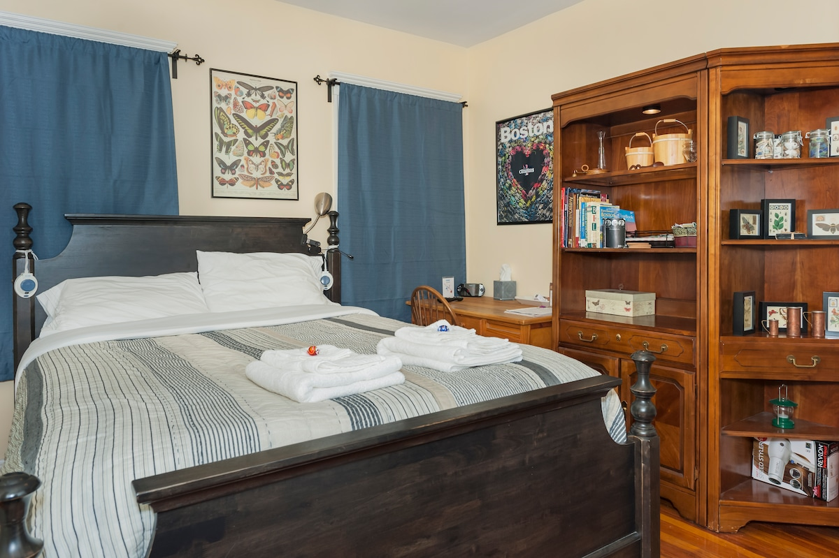 Your comfortable and spacious room with a pillowtop queen bed with soft, fresh sheets and a comfy blanket. Fresh towels with Lindt chocolate truffles, a stocked desk, chairs, a closet with hangers, and blackout curtains so you can sleep in as late as you