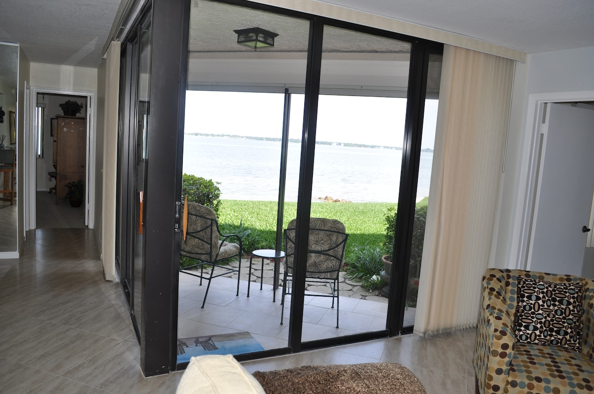 Back patio and grassy area sloping to beach.