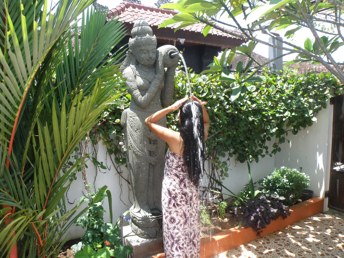 Dewi Sri , the Goddess of rice and prosperity, blesses with a refreshing shower in the sunny Bali day