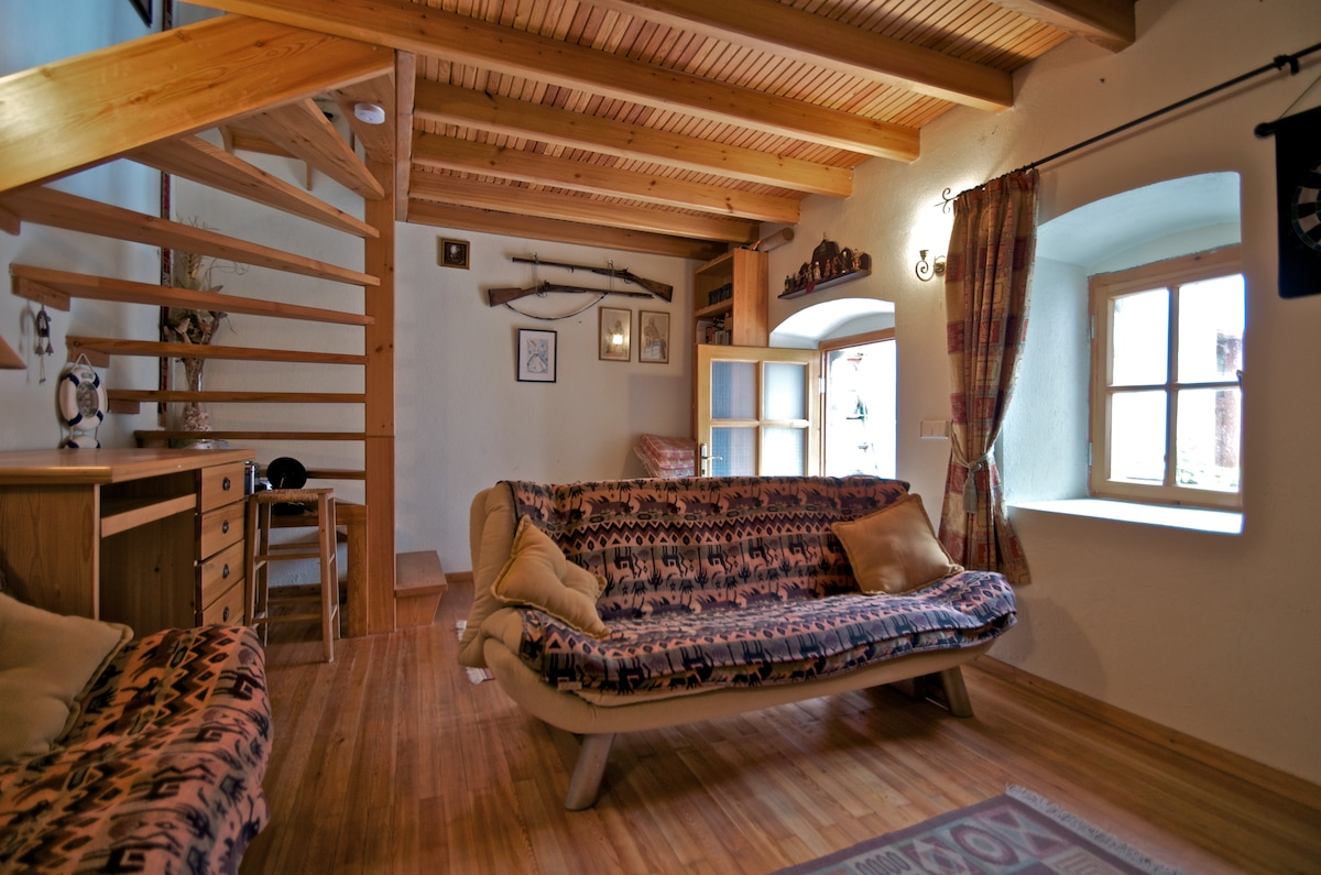 Living room with pine beams, open fire place and 2 sofa beds