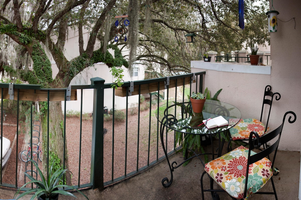 Back patio with view of hundred-year-old oak tree, bird feeder, and plants galore!