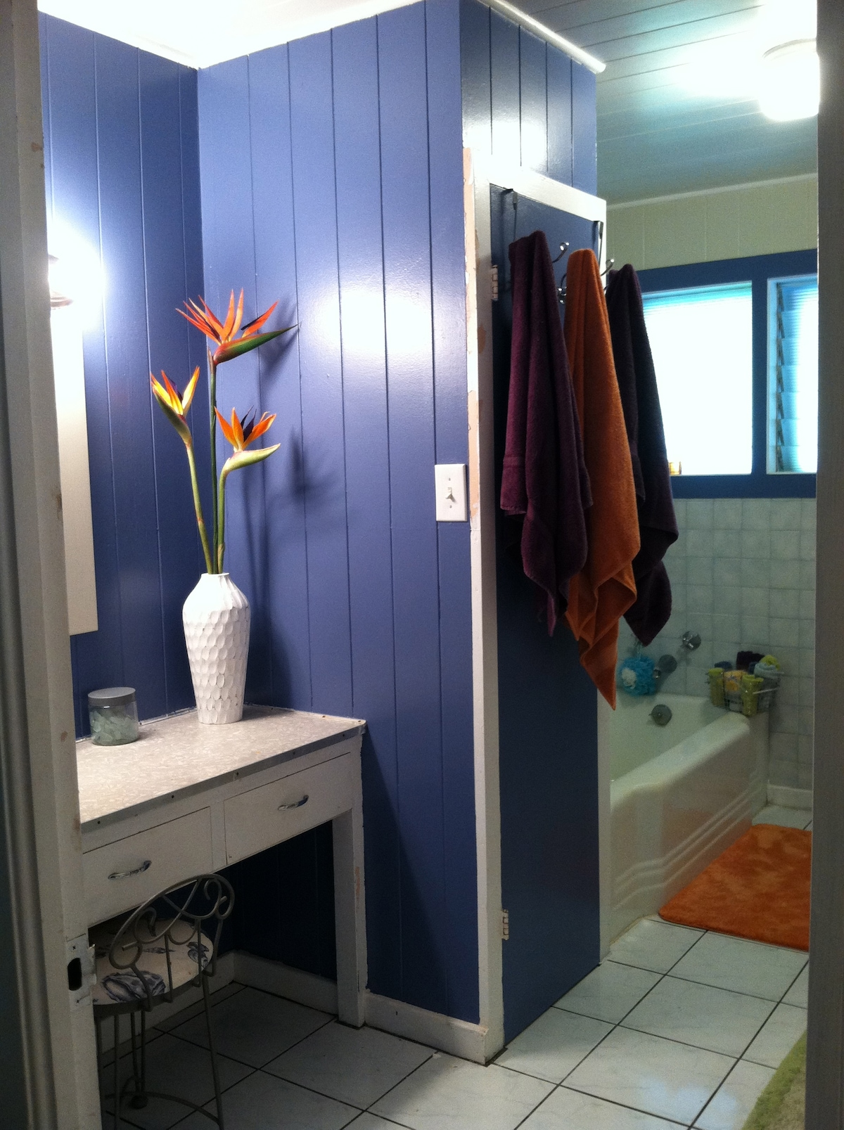 Shared bathroom with shower stall, bathtub and changing area.