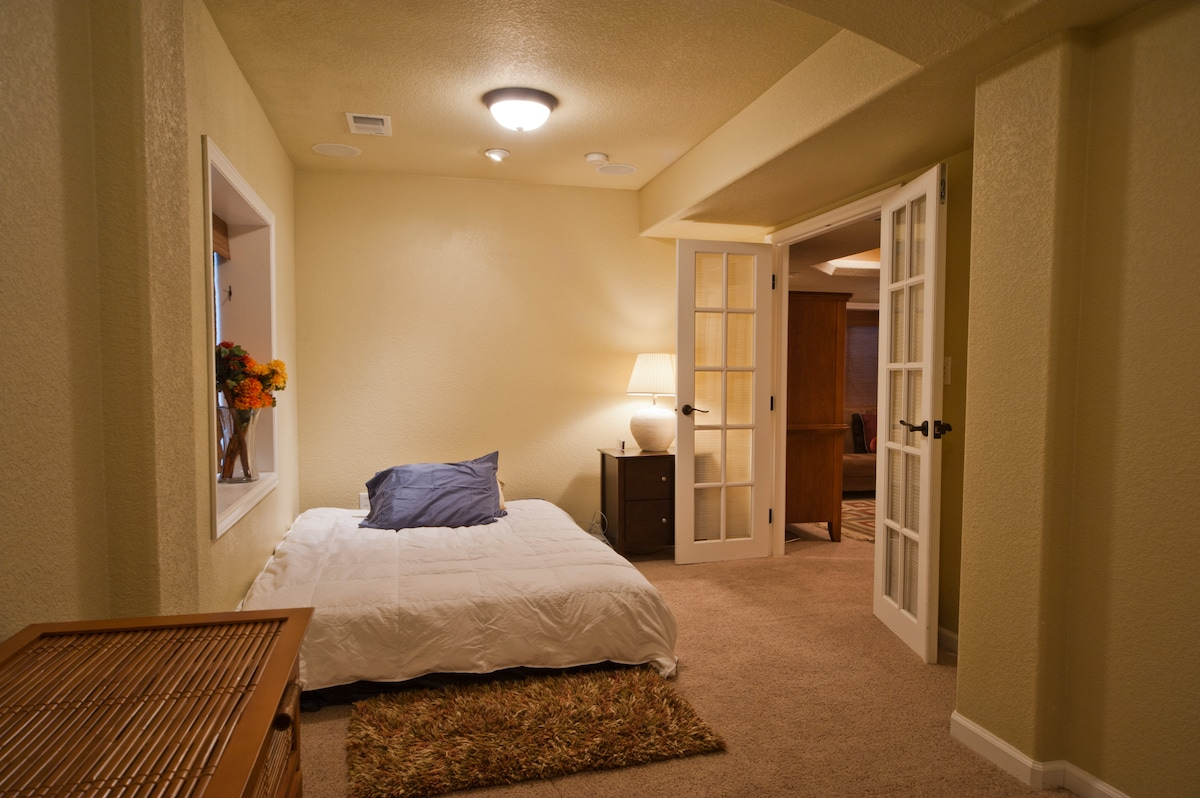 Bedroom with queen sized bed, dresser -- opens into living room