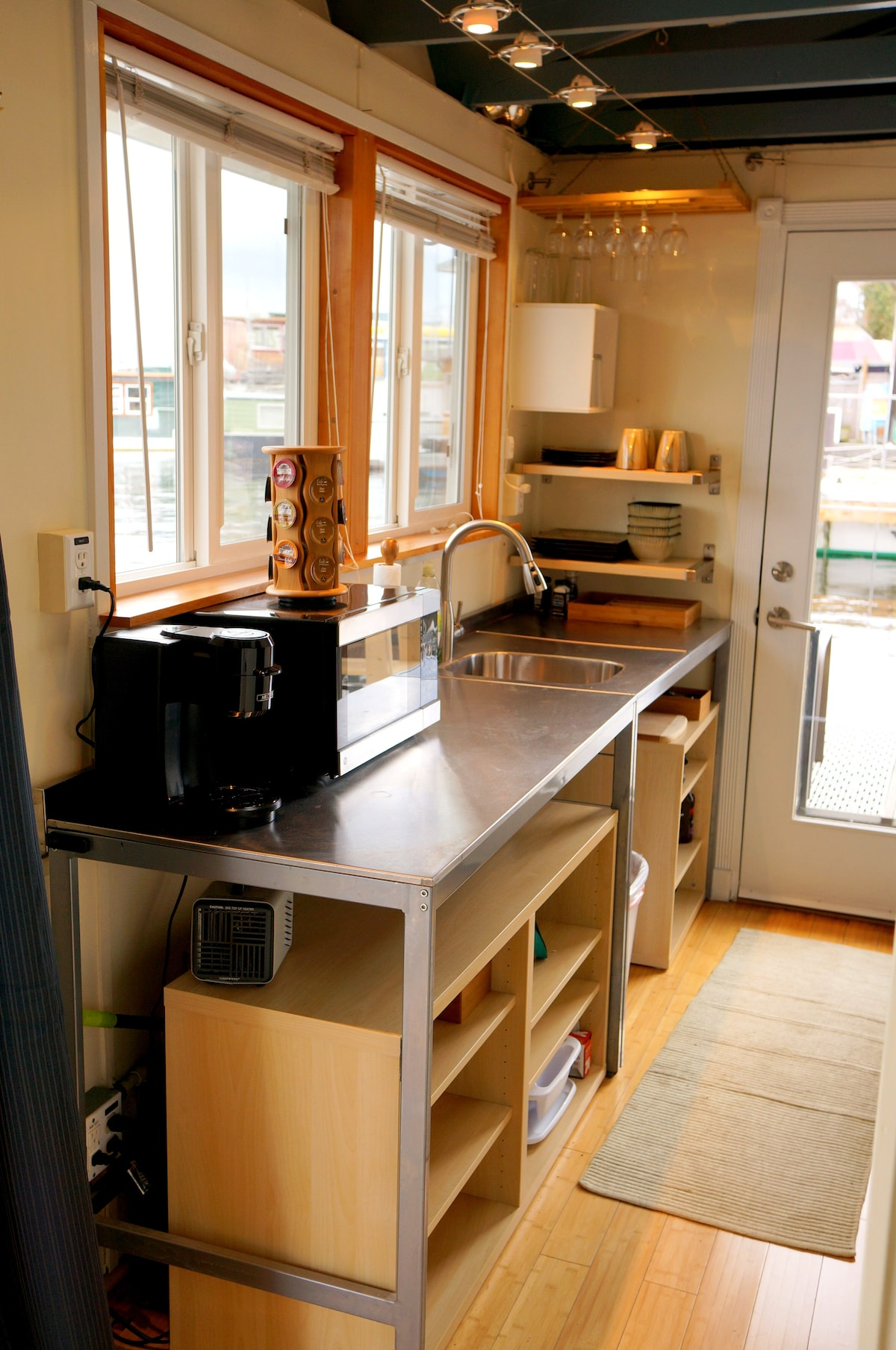 Kitchen includes stainless steel counter tops, microwave, single stove top burner, and plenty of pots and pans to cook with.