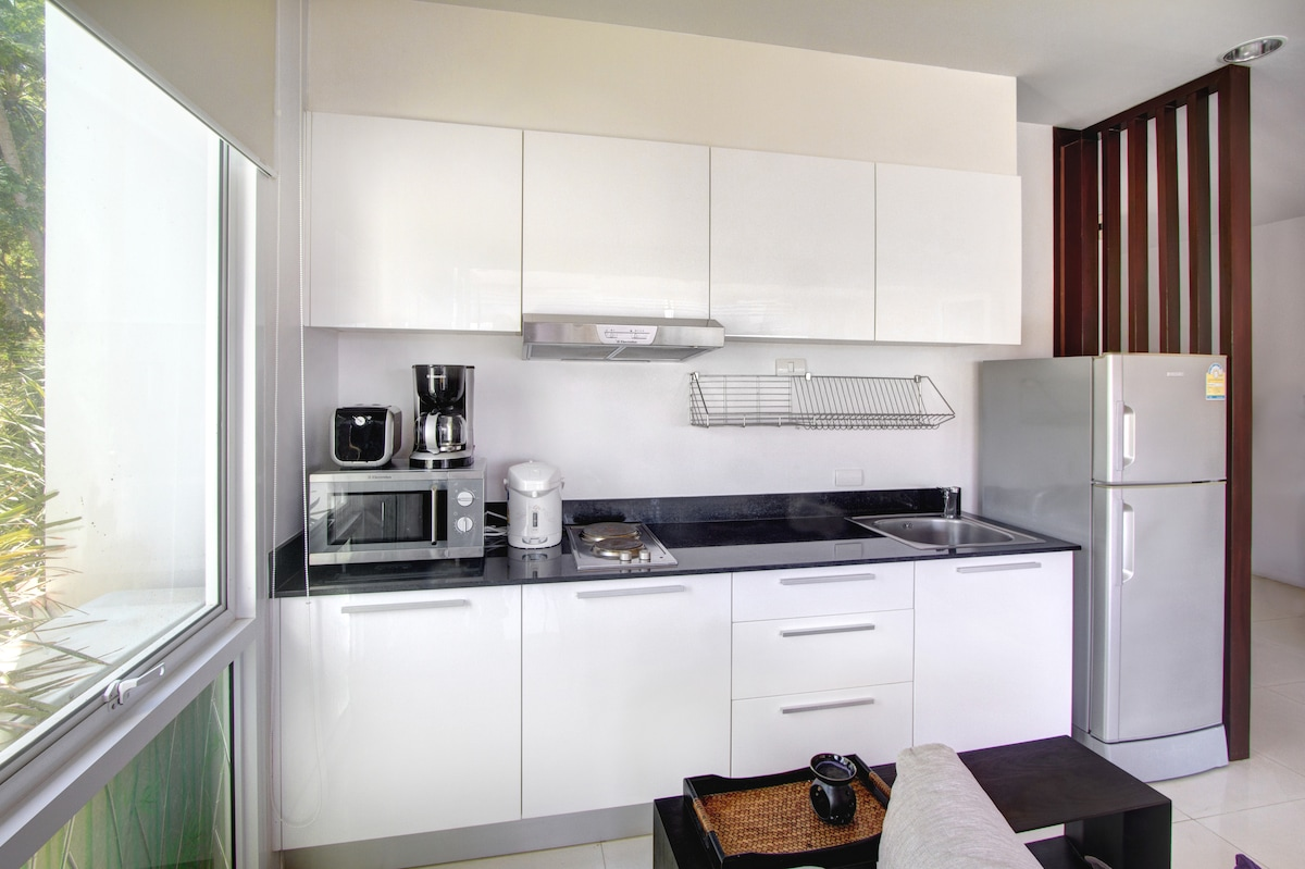 Modern kitchen with microwave, coffee machine and kettle.