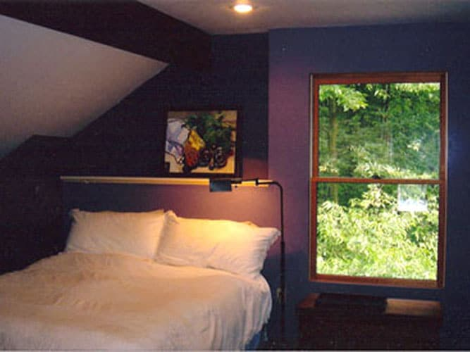 Bedroom overlooking woods and small walled garden area. Original oil painting above bed by the owner/artist.