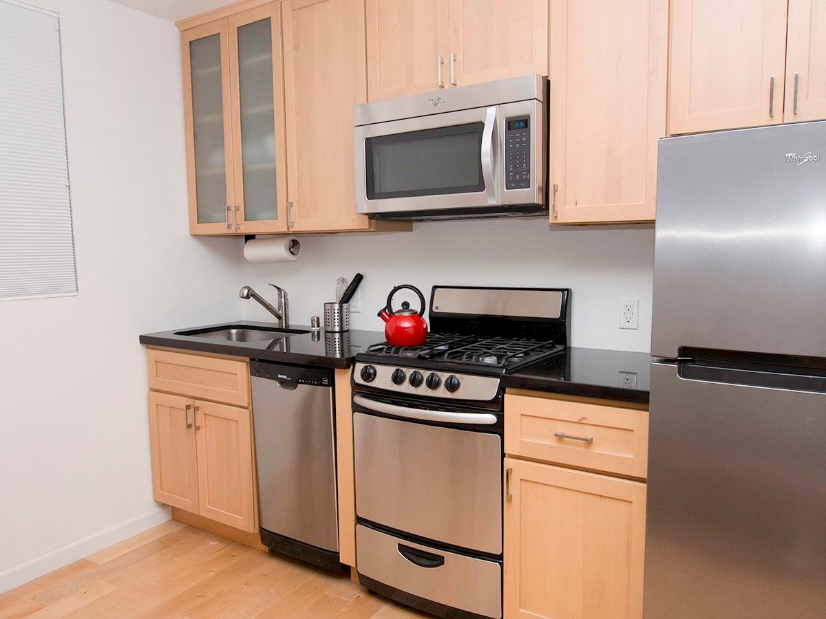 Brand new kitchen with granite countertop, stainless steel dishwasher, gas range, microwave, fridge, and garbage disposal.