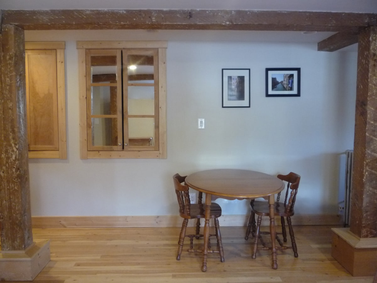 Dinning area with original photographs. Behind the mirrored cupboard door is a huge storage area.