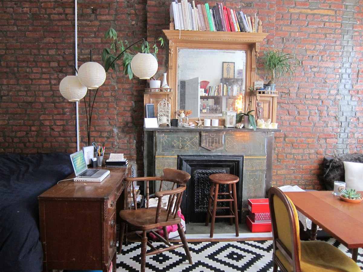 Brick wall and beautiful mantle with plants and books