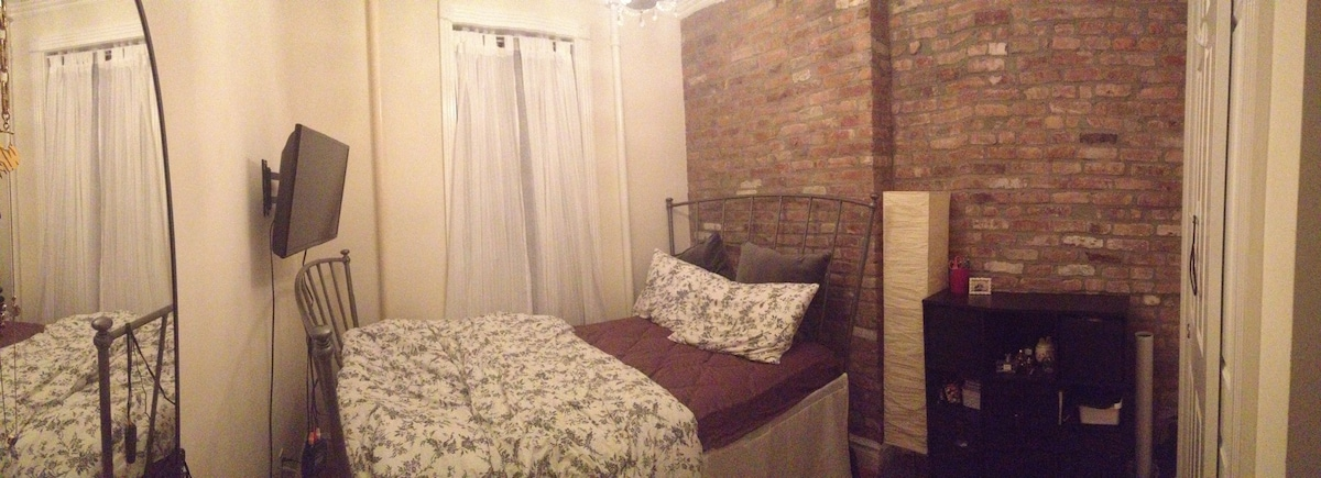 Panorama of bedroom - high ceilings and exposed brick wall