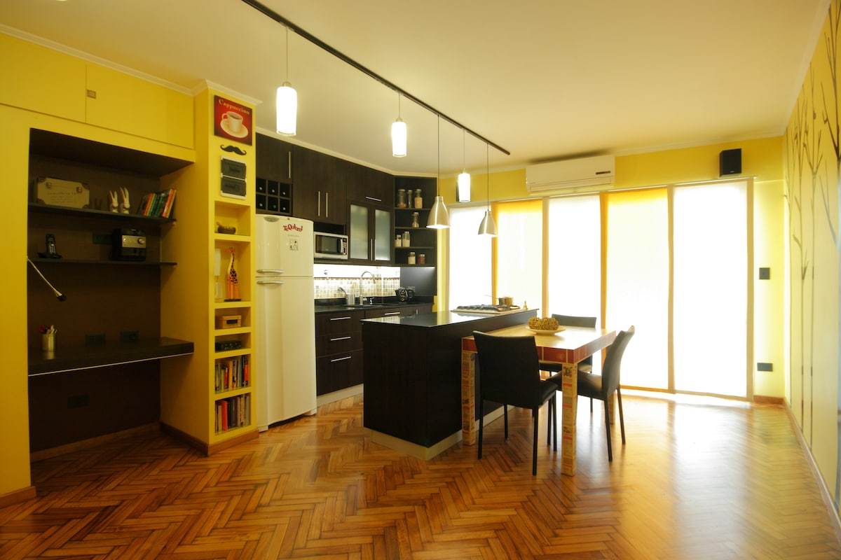 The spacious and living room hosts an open kitchen and a functional working desk.