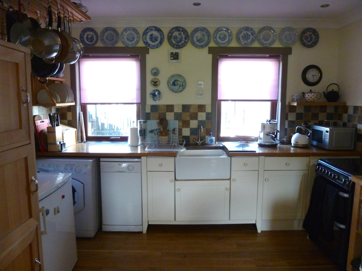 Open plan kitchen with washer dryer, dish washer, fridge, microwave oven and electric cooker.