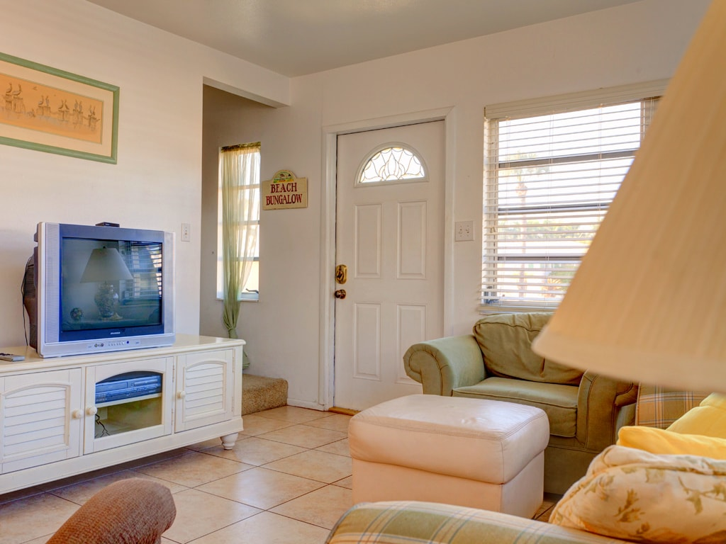 """Our cozy living room has a """"Pottery Barn meets Florida"""" feel. The cool tile floors and crisp white furnishings set the tone in our lovely living room. You'll love the Pottery Barn-esque style with the pastel Florida touches."""