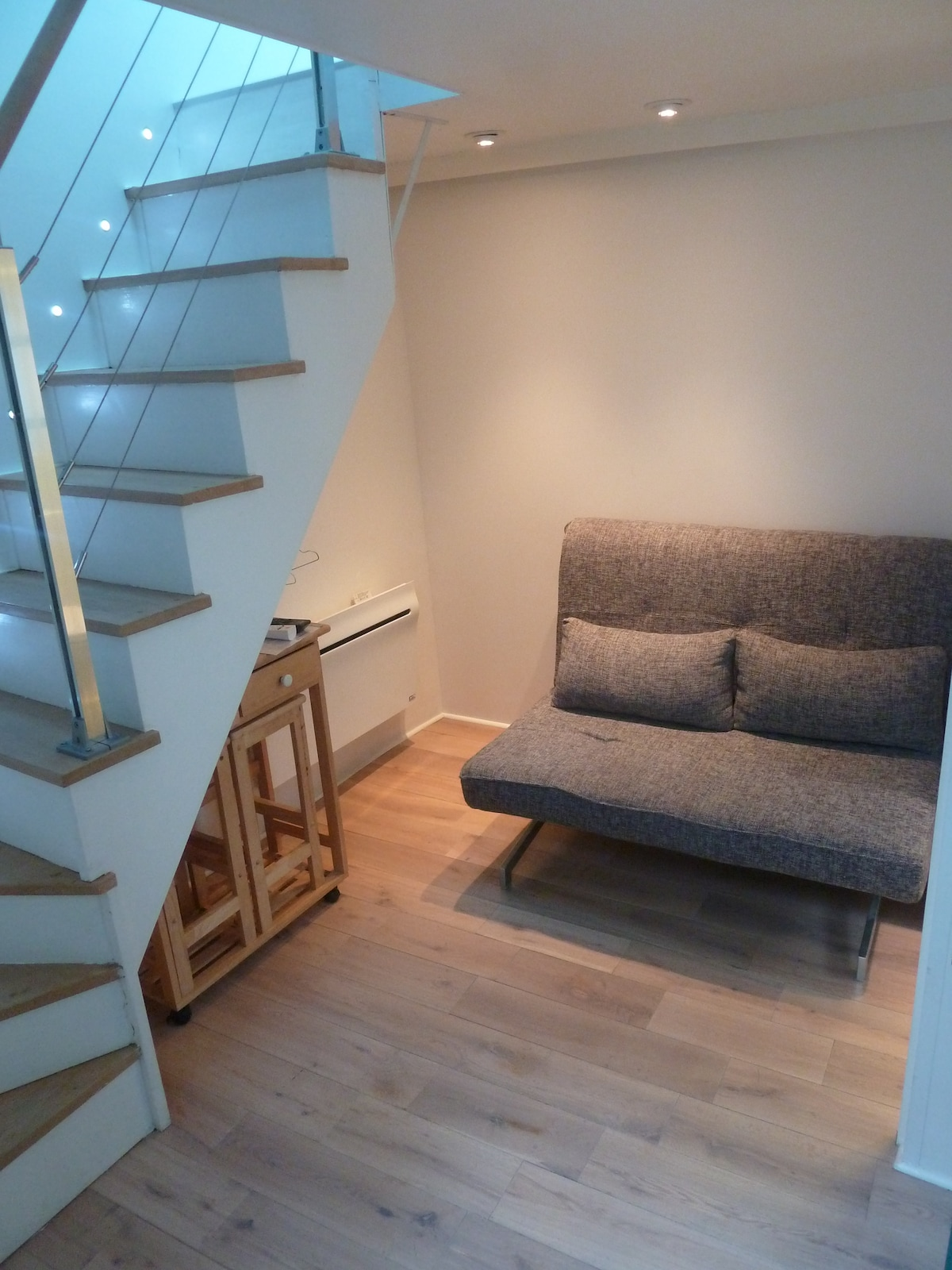 Sofa bed in living room with stairs up to bedroom