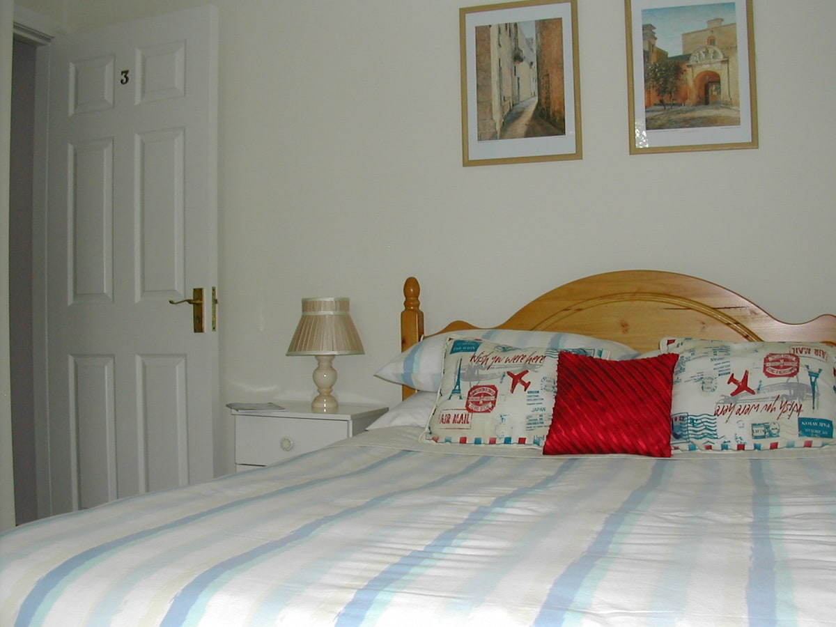 our double en-suite bedroom with prints from europe on wall .