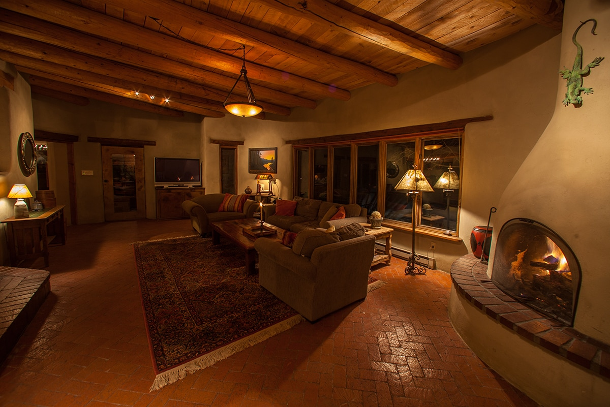 The living room at night with a fire in the kiva.