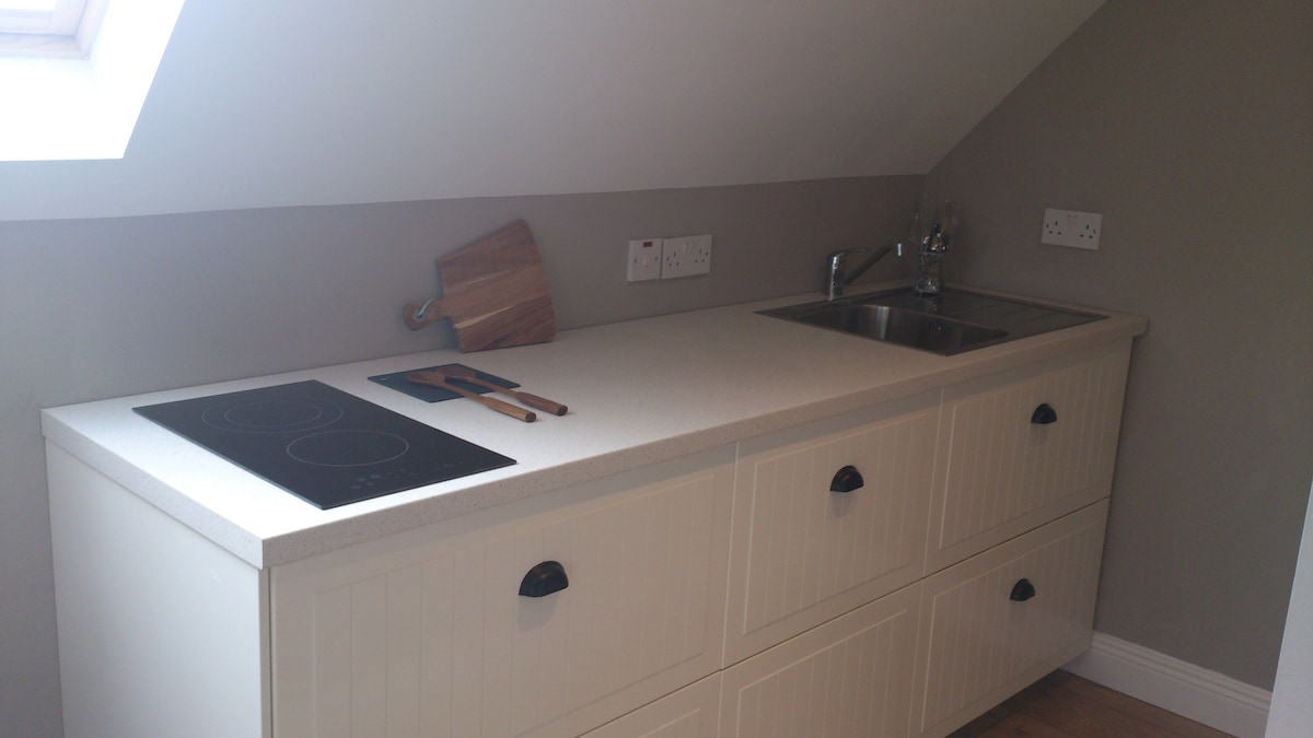 Kitchen with hob/sink and integrated fridge.