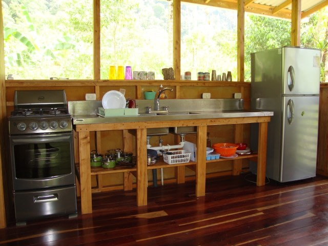 The kitchen in the main room has a fridge, stove/oven, and is equipped with dishes & cookware.