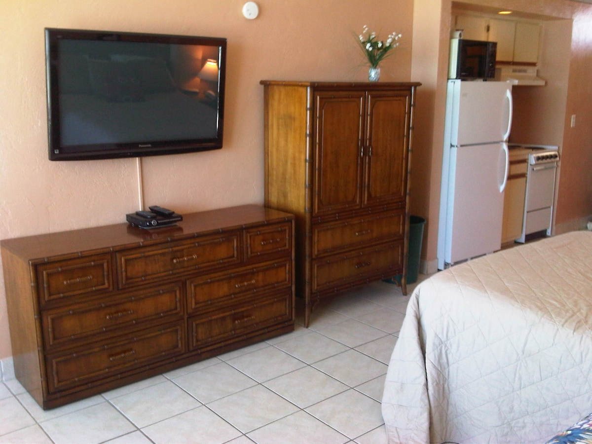 """Dressers and 42"""" flatscreen TV with cable ,HBO, DVD player. To the right is a the fridge, microwave, sink, stove"""