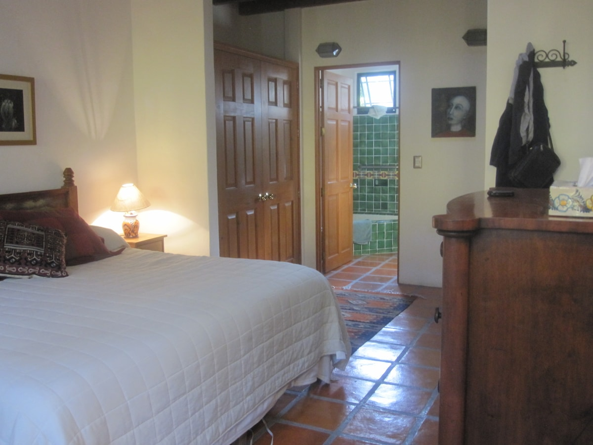 Master bedroom, king bed, antique dresser, master bath through door.