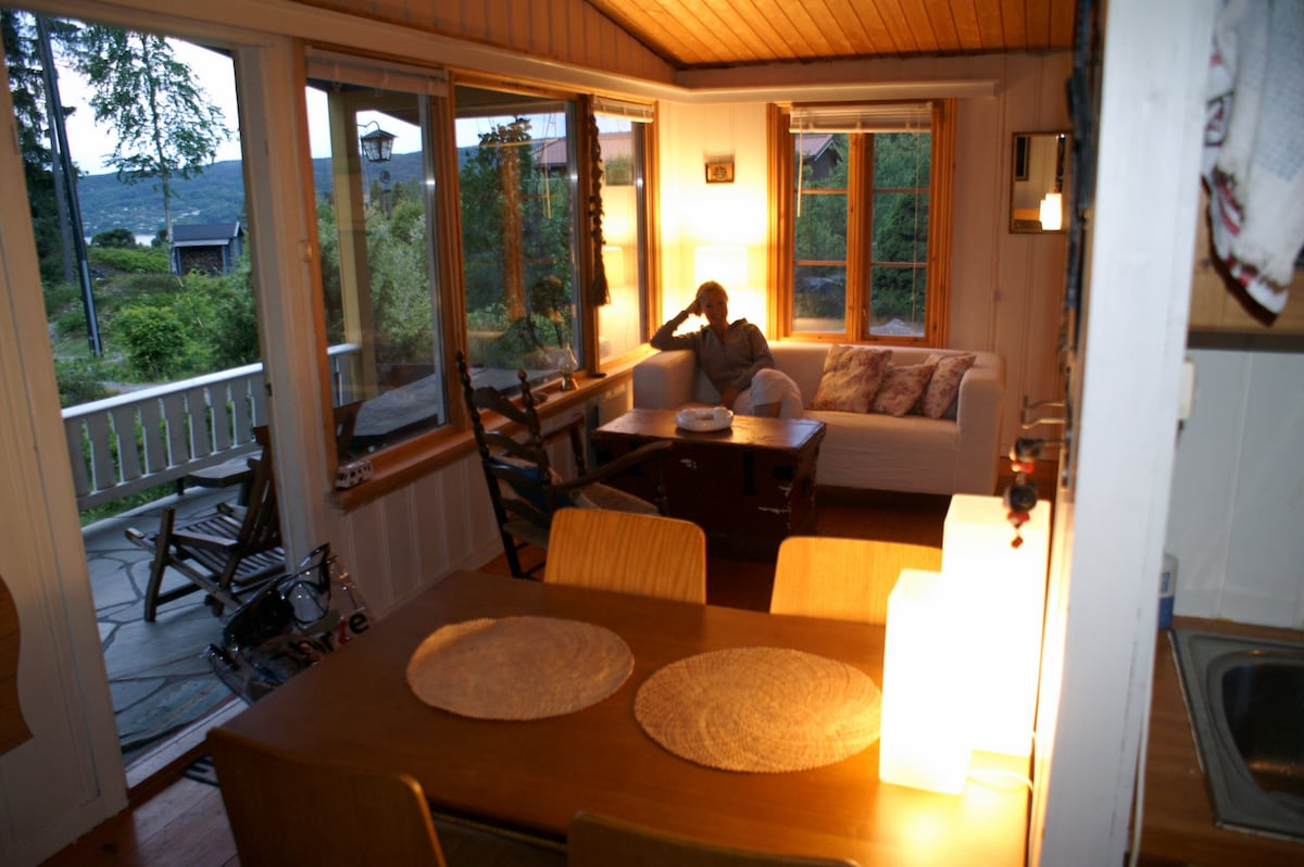 Dining table in the front, a view of the porch and the sitting group by the window.