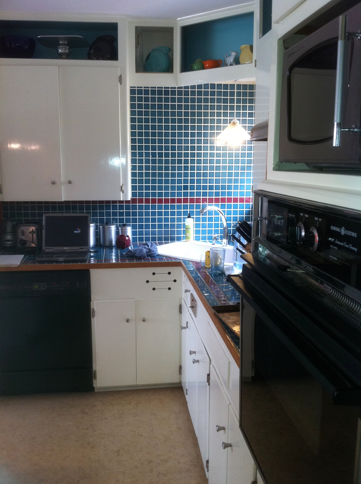 Kitchen with corner sink, dishwasher, window looking into backyard, gas cooking, stove and microwave.