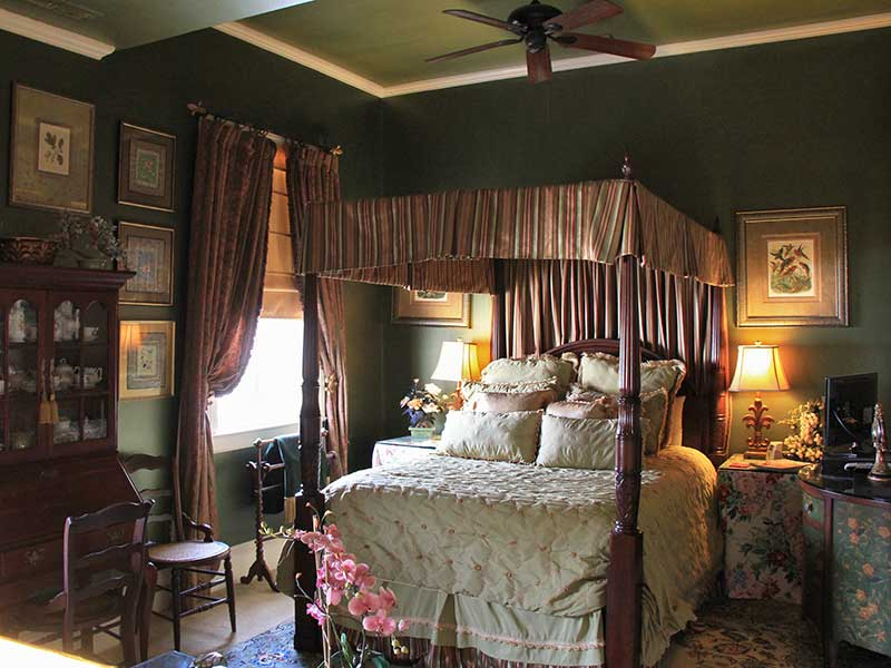 Queen canopy bed, floral botanical artwork, oriental rugs.